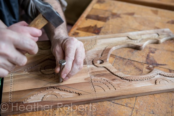 His hands seem so little next to this craftsman's.